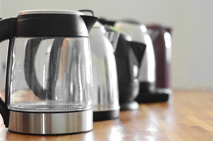 Five electric tea kettles on brown table